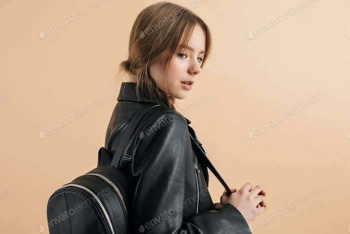 Young attractive school girl with two braids in leather jacket with black backpack