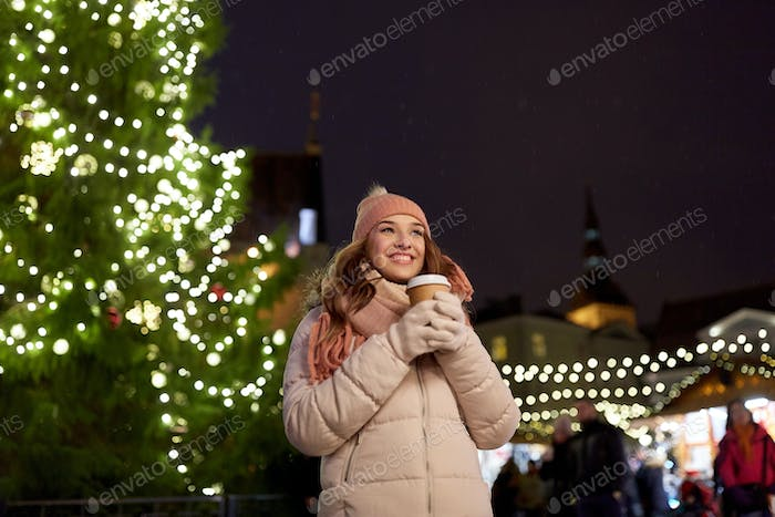 happy young woman with coffee at christmas market