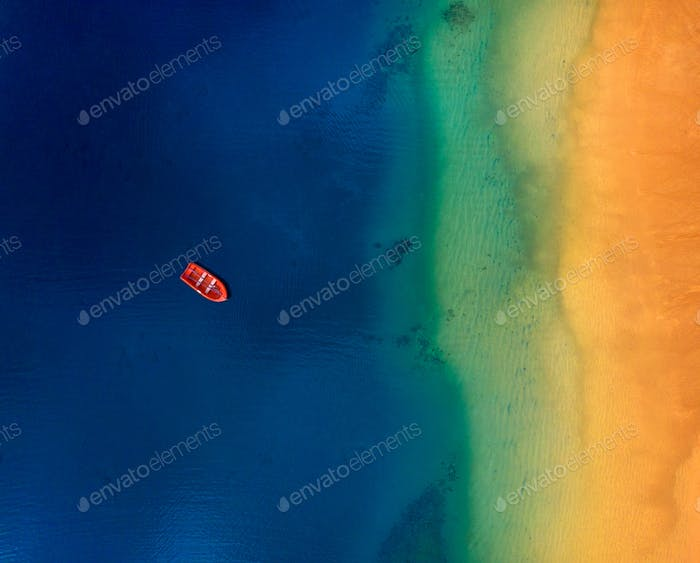 Aerial view of a lonely red boat anchored off the coast of Las Teresitas beach