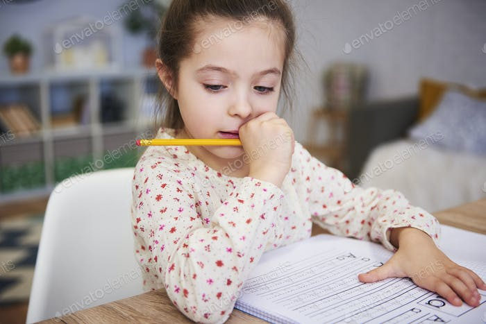 Focused girl doing her homework at home
