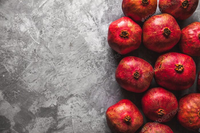 Pomegranate fruit on rustic grey background with copy space for your text