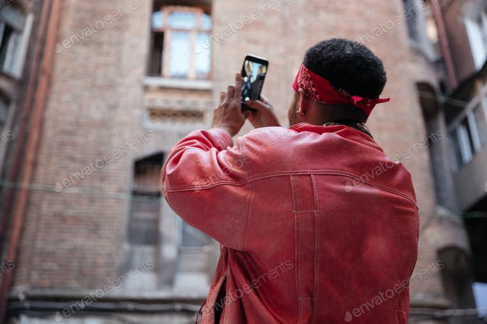Guy in leather jacket taking picture with mobile phone