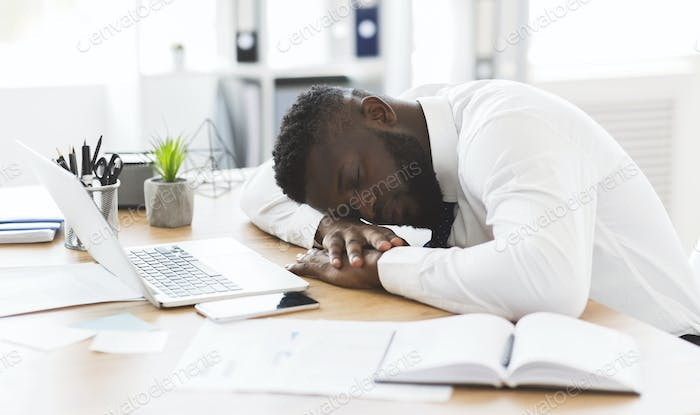 Exhausted african worker sleeping on his workplace