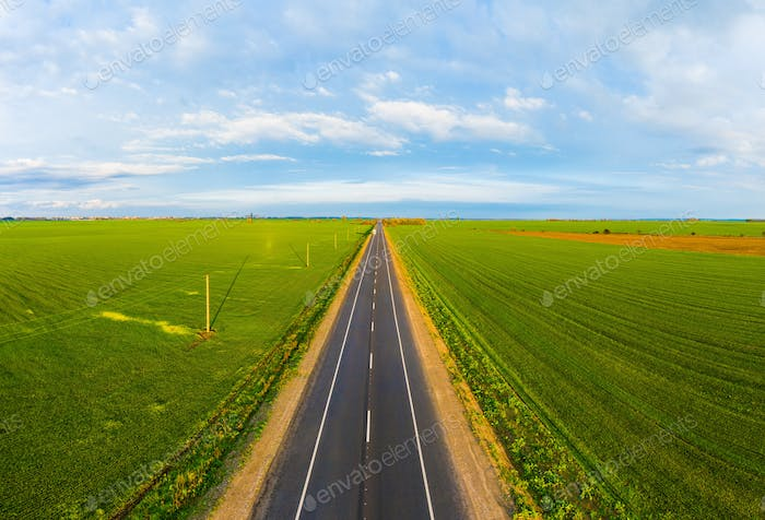 Summer landscape with green field with traffic on the road