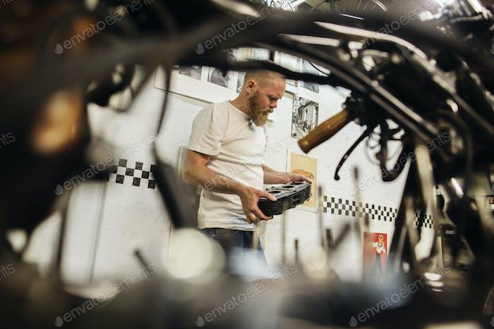 Reifer Mann hält Fahrzeug Teil in der Werkstatt
