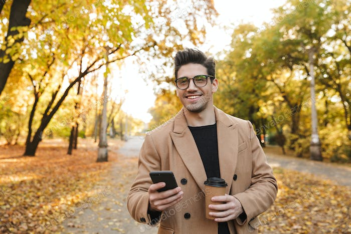 Image of handsome european man using cellphone and smiling in autumn park