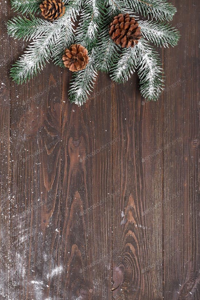 Weihnachts-Grußkarte mit Weihnachtskegel und Tannenzweig auf dunklem Holzhintergrund. Oben