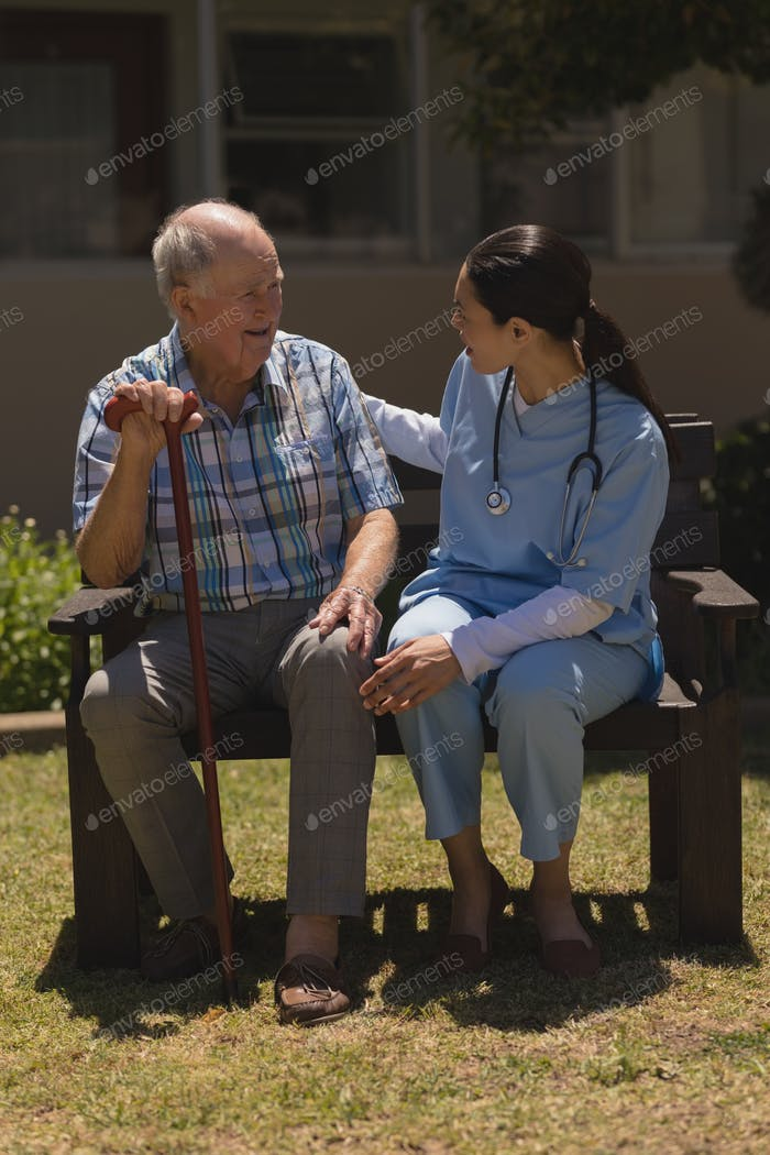 Female doctor talking with senior man with his cane  while sitting on bench in garden