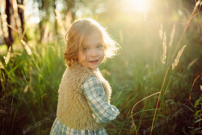 Cute smiling girl at the green field in sunset