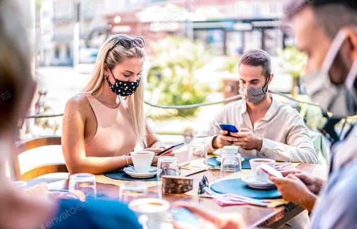 Junge Freunde nutzen mobile Smartphones an der Kaffeebar