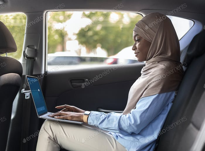 Black Muslim Businesswoman Using Laptop In Car While Going To Work
