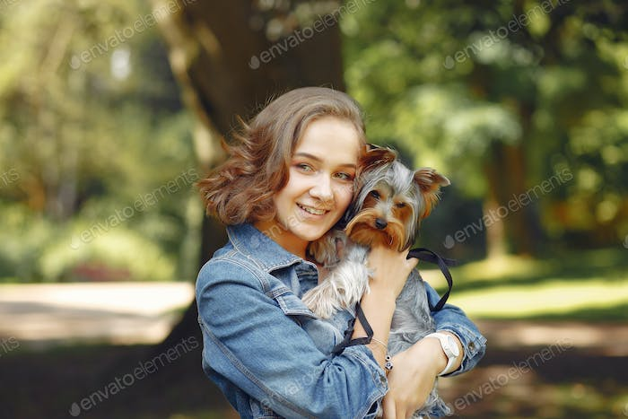 Cute girl in blue jacket playing with little dog