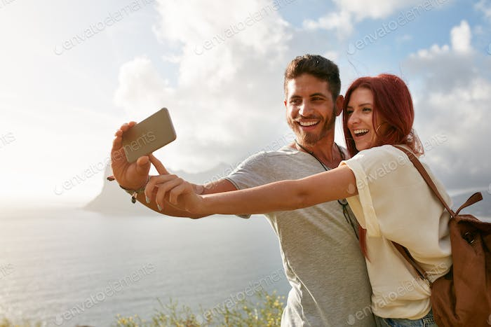 Happy couple making selfie with smart phone