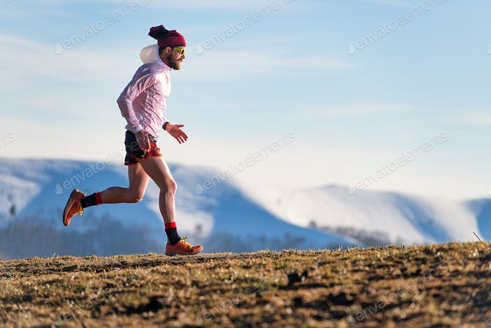 Mountain race. Training of an athlete between meadows and snow
