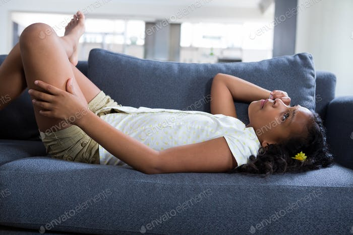 Side view of thoughtful girl lying on sofa
