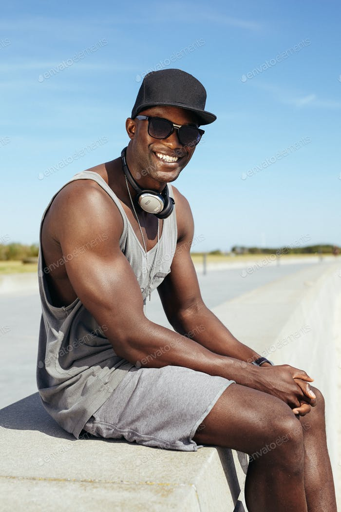 Happy young african man sitting on a promenade