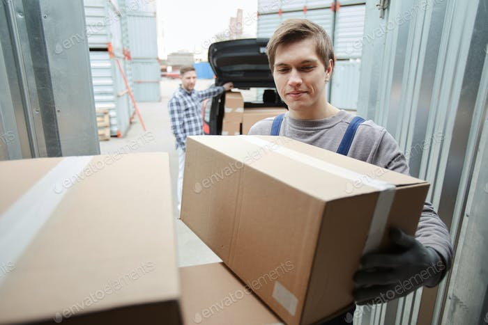 Smiling worker assisting client to loading car