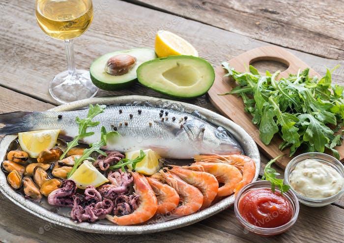 Frischer Seebass mit Meeresfrüchten auf dem Tablett