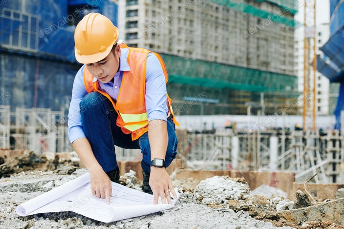Contractor examining building blueprint