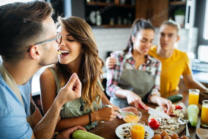 Grupo de amigos felices riendo y hablando mientras preparaba las comidas en la cocina