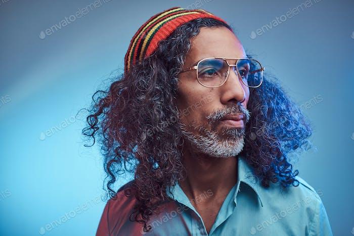 Studio portrait of African Rastafarian male wearing a blue shirt and beanie.