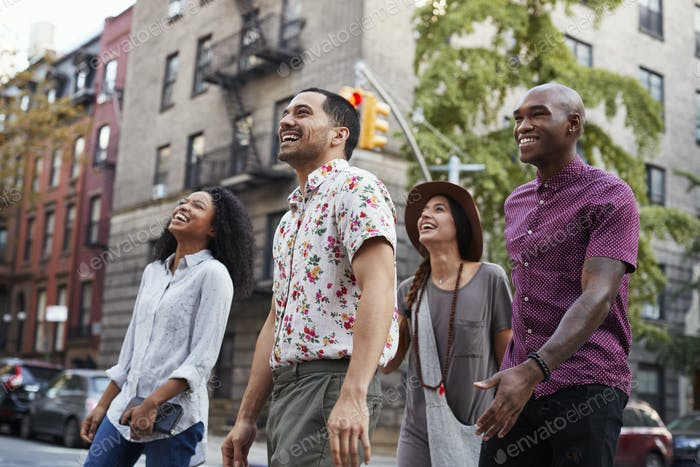 Group Of Friends Walking Along Urban Street In New York City