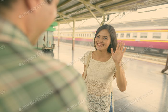 Persian tourist man and young Asian tourist woman together at the railway station