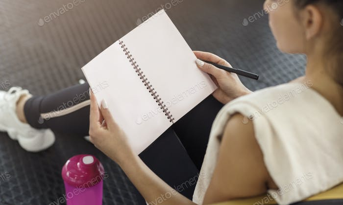 Unrecognizable woman writing her workout schedule in notebook, closeup