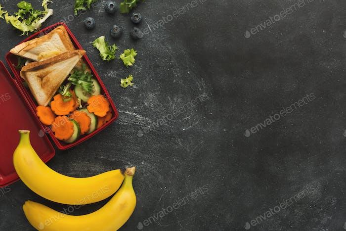 Lunchbox mit gesundem Essen auf schwarzem Tischhintergrund