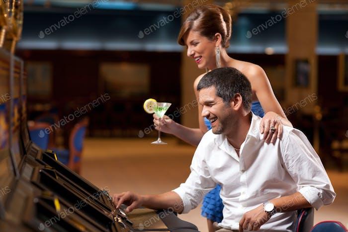elegant couple playing the slot machine