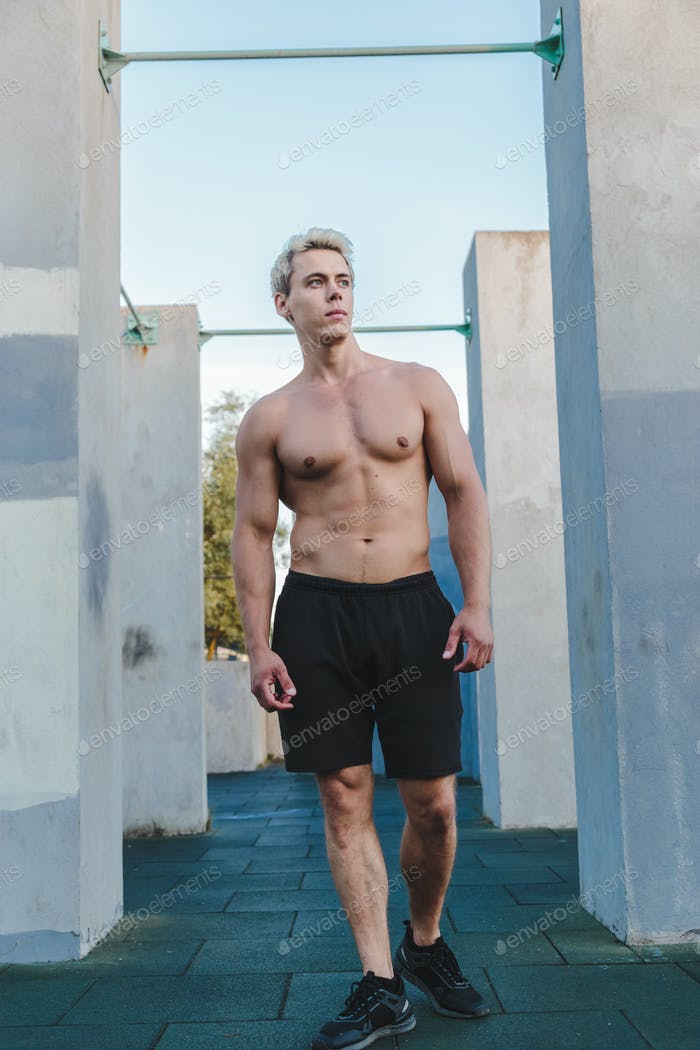 Natural portrait of young athletic shirtless man standing near concrete wall.