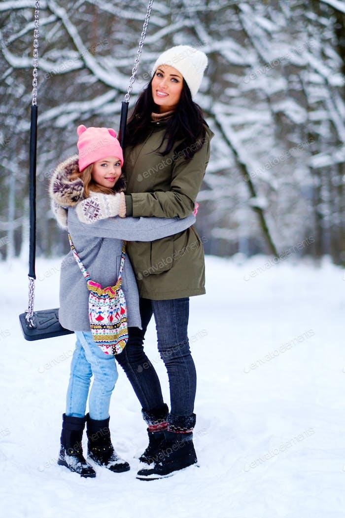Kleines Mädchen mit ihrer Mutter im freien in ein Schnee