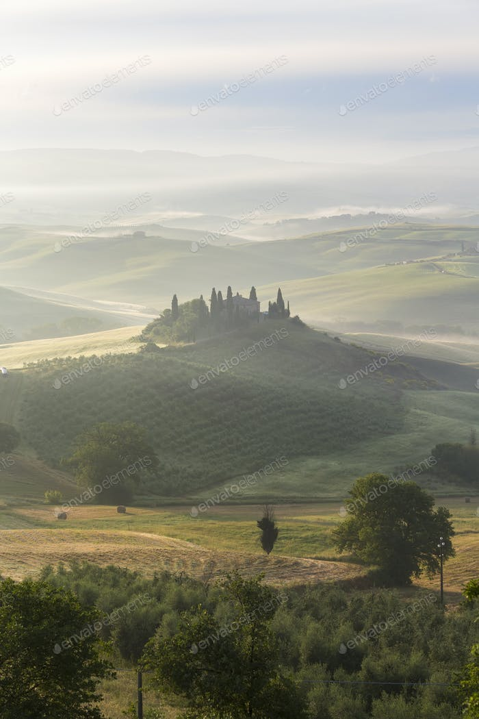 Sunrise across a misty Italian landscape of rolling hills and cypress trees