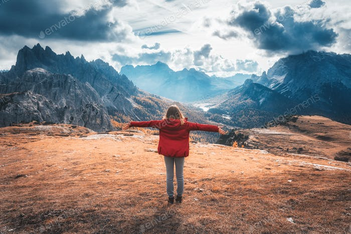 Young woman with raised up arms and mountains at sunset