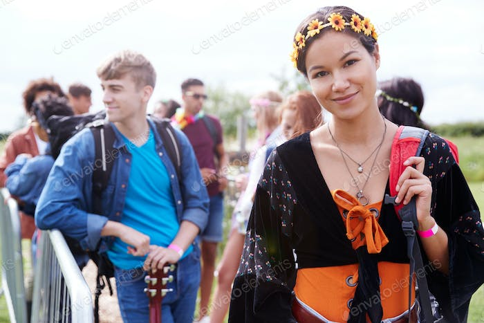Portrait Of Young Woman Waiting Behind Barrier At Entrance To Music Festival Site