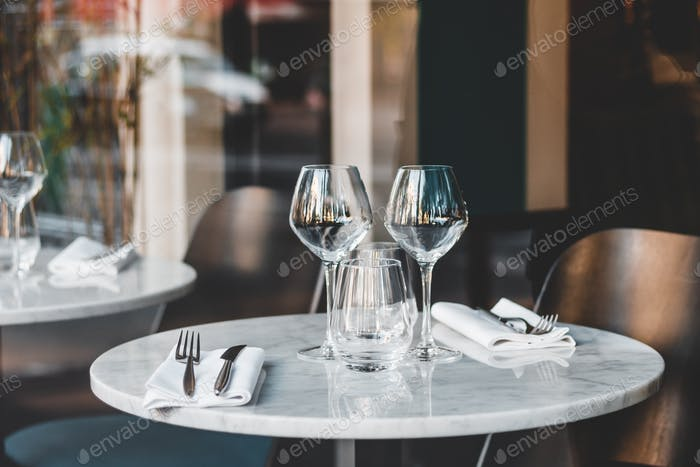 Table setting in a French restaurant. View through a window from a street.