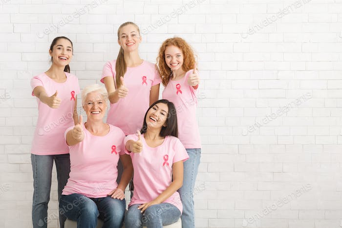 Volunteers In Breast Cancer T-Shirts Gesturing Thumbs-Up Over White Wall