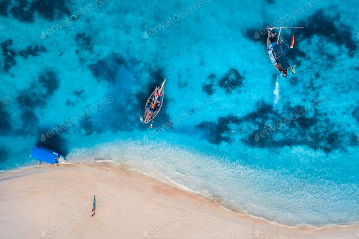 Aerial view of the fishing boats in clear azure water at sunrise
