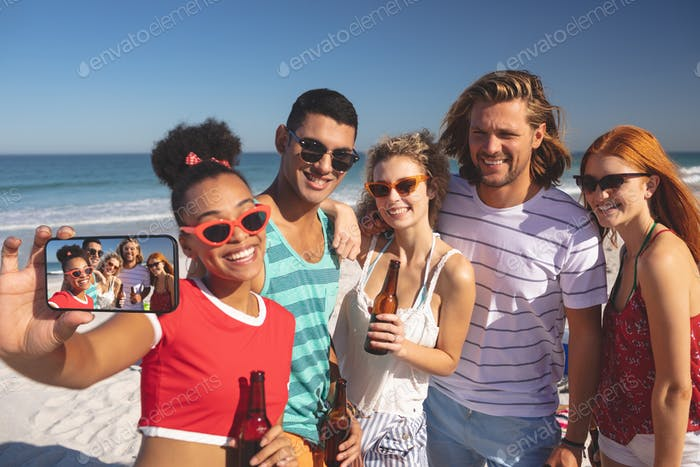 Front view of group of young diverse friends taking selfie with mobile phone on the beach