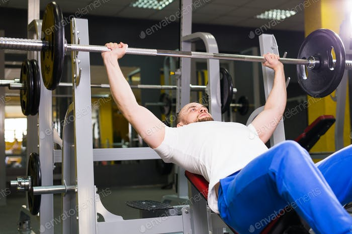 Sport, fitness, training and people concept - Man during bench press exercise in gym
