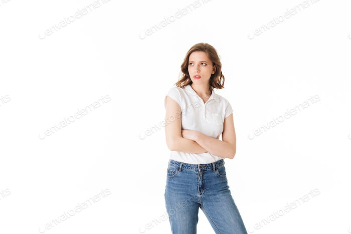 Portrait of young upset lady standing in t shirt and jeans and sadly looking aside