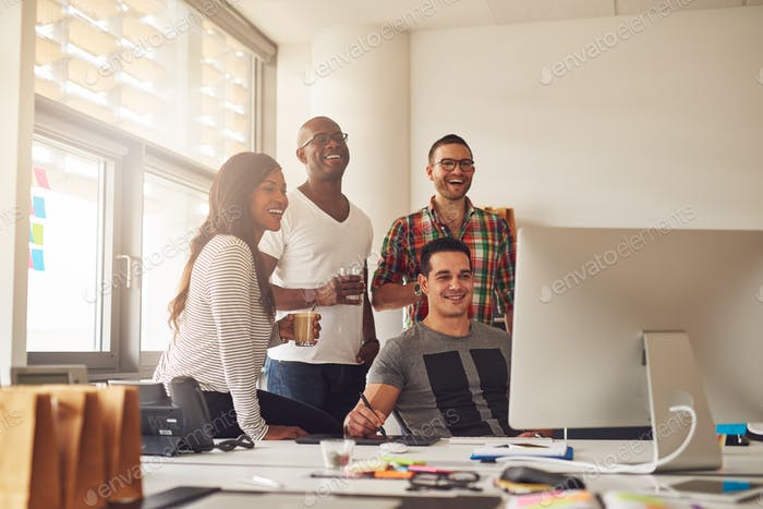 Laughing woman and men at computer in office