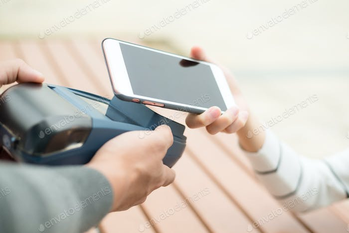 Female paying with NFC technology on smart phone