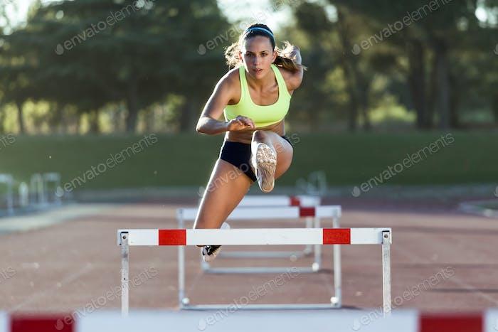 Junge Sportler springen über eine Hürde während des Trainings auf Renntrac