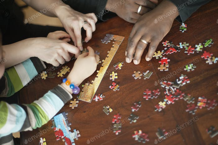Cropped image of family solving jigsaw puzzle at table