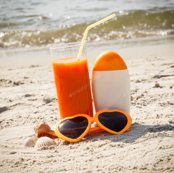 Karottensaft, Sonnenbrille und Sonnencreme am Strand, Konzept von Vitamin A und schöne, dauerhafte Bräune