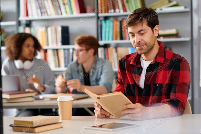 Handsome student with open book while sitting by desk in college library