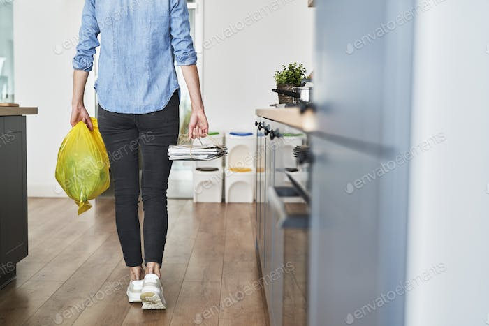 Woman about to throw away segregated paper and plastic