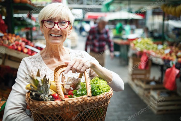 Senior woman buying vegetables at the green market