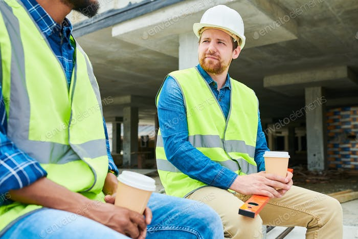 Construction engineer listening to colleague